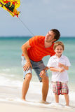Father and son flying kite together. Portrait of happy dad and son flying kite together royalty free stock image