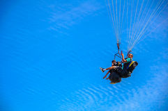 Father and son flying on paraglider together in tandem royalty free stock images