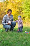The father, the son and a football ball. Young family in autumn forest stock photography