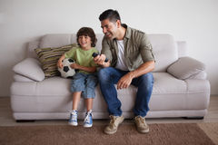 Father and son with football watching tv in the living room Stock Photo