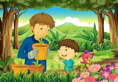 A father and a son at forest watering the plants Stock Image