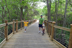 Father Son Forest Wooden Bridge. Father and son walking with child's bike over a wooden bridge in the forest or park Royalty Free Stock Photos