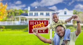 Father and Son In Front of Real Estate Sign and Home Stock Photo