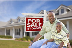 Father and Son In Front of For Sale By Owner Sign and House. African American Father and Son In Front of For Sale By Owner Real Estate Sign and House stock images