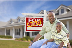 Father and Son In Front of Sold For Sale Sign and House. African American Father and Son In Front of Sold For Sale Real Estate Sign and New House Royalty Free Stock Photos