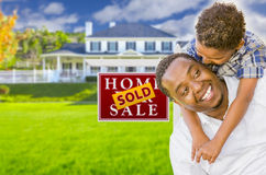 Father and Son In Front of Sold Sign and House Stock Image