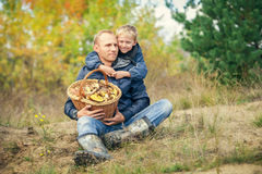 Father and son with full basket of mashrooms on the forest glade Royalty Free Stock Photo