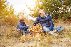 Father and son with full basket of mushrooms rest  in forest Royalty Free Stock Image