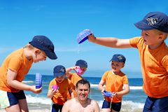 Father and son fun at beach. Father and son enjoying time together, playing at the beach, splashing water. Montage photo Royalty Free Stock Image