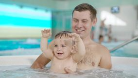 Father and son funny in water pool. Leisure and swimming at holidays stock footage