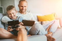 Father and son game players funs sit together at home on cozy sofa, using the tablet and gamepad royalty free stock images