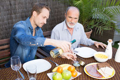Father and son in garden. Drinking wine Royalty Free Stock Photography