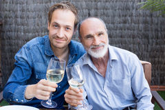 Father and son. In garden drinking wine Royalty Free Stock Photos