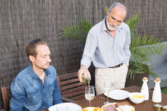 Father and son in garden. Having some food Stock Image
