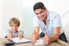 Father and son gesturing thumbs up while doing homework. Portrait of happy father and son gesturing thumbs up while doing homework at table Stock Photography