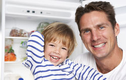 Father And Son Getting Snack From The Fridge Royalty Free Stock Photos