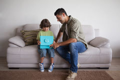 Father and son with gift box sitting in living room Royalty Free Stock Photo