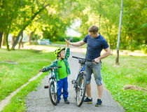 Father and son give high five while cycling in the park stock photo