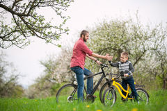 Father and son give high five. While cycling in the spring garden, against the background of blooming trees and fresh greenery Stock Photography