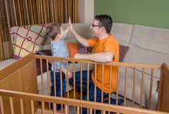 Father and son giving five for success in a home. Portrait of father and son giving five for a success in the assembly of cot for a newborn at home. Family royalty free stock photos