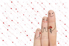 Father and son are giving flowers their mother. Conceptual family finger art. Stock Image. Happy Mother's Day, birthday and 8 March creative and funny love Stock Photo