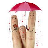 Father, and son are giving flowers their mother  staying under umbrella with falling hearts. Royalty Free Stock Photos