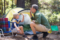 Father and son giving high five by tent at campsite Royalty Free Stock Images