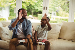 Father and son giving high five to each other while playing video game. At home stock photography