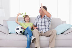 Father and son giving high-five while watching soccer match Royalty Free Stock Images
