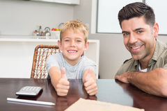 Father and son giving thumb up smiling at camera at the table Stock Photo