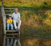 Father and son go fishing on the lake, family vacation on the ri Stock Photos