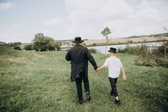Father son go meadow lake together black. Father and son, the peasants go along the meadow to the lake together in black clothes and white shirts stock photo