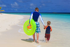 Father and son go swimming at the beach Stock Photo