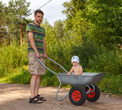 Father and son go for a walk. Baby stands in barrow Stock Photos