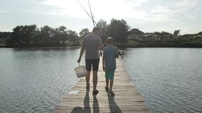Father and son going fishing with rods on lake stock video footage