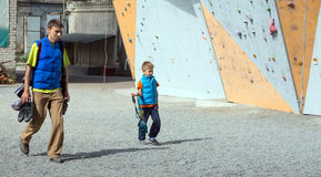 Father and son going to climbing wall Stock Photo