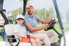 Father and son in golf cart. Royalty Free Stock Image
