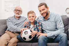 Father, son and grandfather sitting together on couch in living room. With soccer ball royalty free stock photography