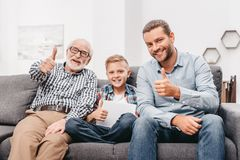 Father, son and grandfather sitting together on couch in living room and showing stock image
