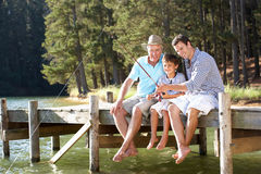 Father,son and grandson fishing together. Father,son and grandson sat on pier fishing together Stock Photography