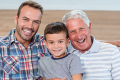 Father, son and grandson sitting on sofa. And smiling in living room Stock Photos