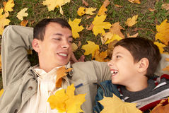 Father and son on the grass. Happy father and son lying on the grass in the autumn day Stock Image