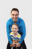 Father and son on gray. Adult male embraces little boy and smile on gray background - father and son - family relations Royalty Free Stock Images