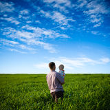 Father and son on green field Stock Photos