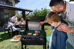 Father and son grilling meat while family sitting at table outdoors royalty free stock photos