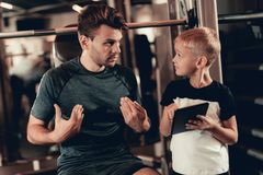 Father And Son In Gym. Information On Tablet. stock photos