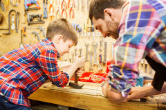 Father and son with hammer working at workshop. Family, carpentry, woodwork and people concept - father and little son with claw hammer pulling nail out of wood Royalty Free Stock Photo