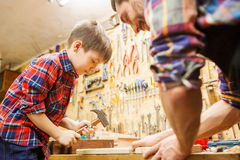 Father and son with hammer working at workshop. Family, carpentry, woodwork and people concept - father and little son with hammer hammering nail into wood plank Royalty Free Stock Photos