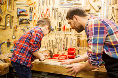 Father and son with hammer working at workshop. Family, carpentry, woodwork and people concept - father and little son with hammer hammering nail into wood plank Royalty Free Stock Image