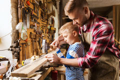 Father and son with hammer working at workshop. Family, carpentry, woodwork and people concept - father and little son with hammer hammering nail into wood plank Royalty Free Stock Photo